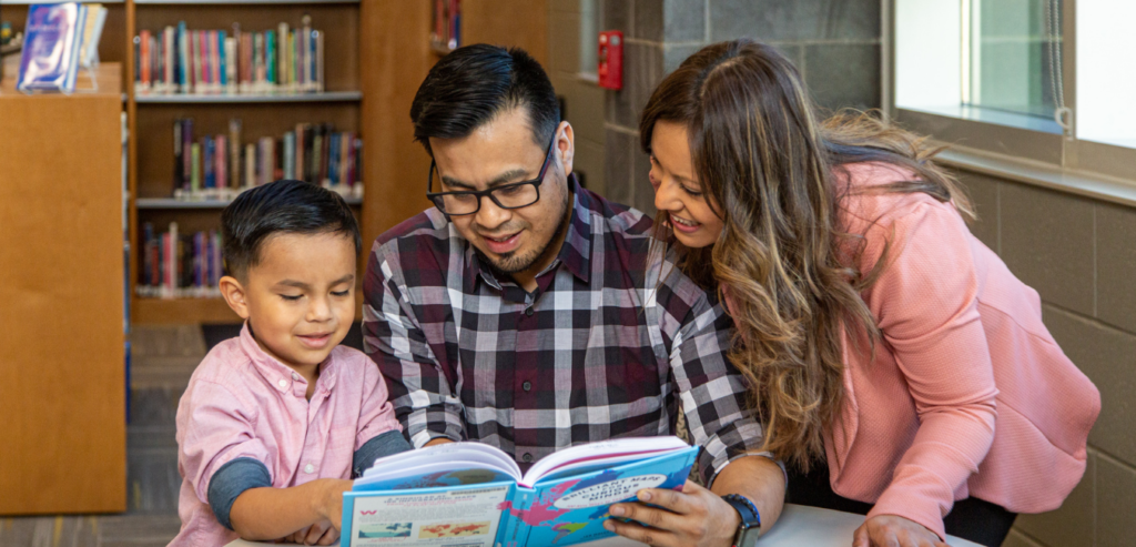 Image of Young child reading a book with parents.